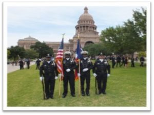 Two T S U Police is holding a U S And a Texas Flag on their hand and getting ready for the parade